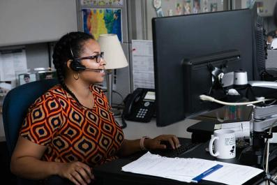 LGA call center representative in office with headset on