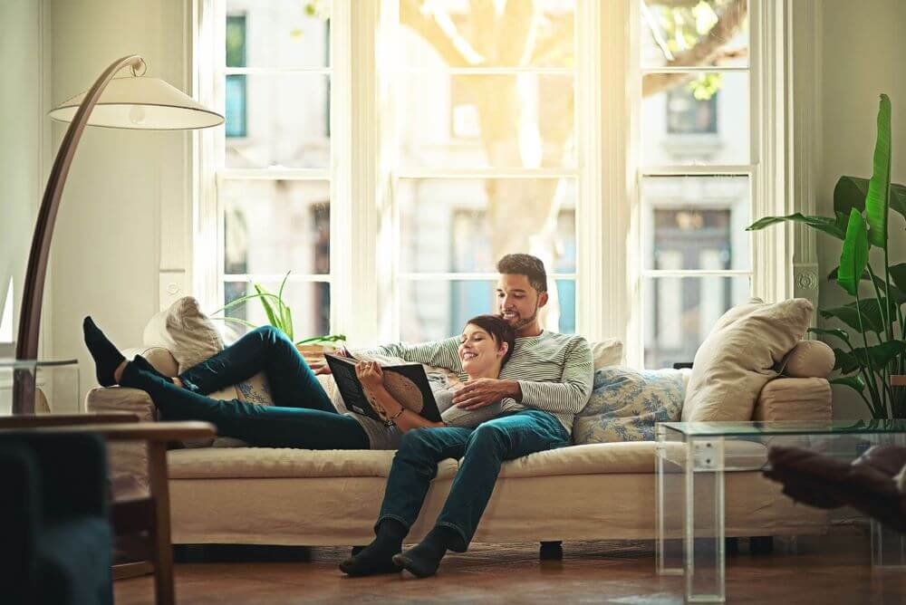 couple-on-couch-reading-book-together