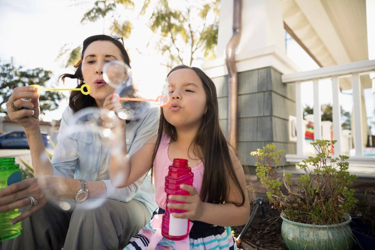 woman-blowing-bubbles-with-little-girl-outside