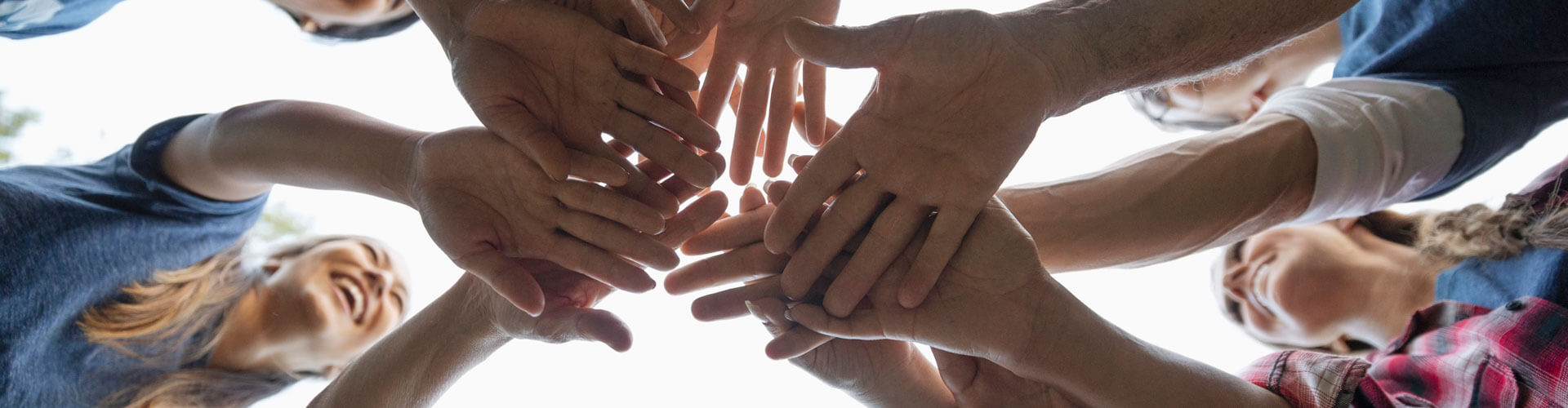 group-of-volunteers-with-hands-together-in-circle